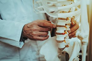 Osteopathic medicine doctor pointing to spine on skeletal system, what is osteopathic medicine