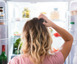 photo of a woman looking at her refrigerator