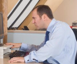 man sitting at desk with bad posture