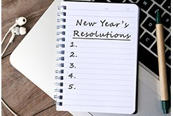 Photo of notebook that says New Years Resolutions with a pen and headphones