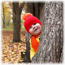 Photo of a toddler peeking out from behind a tree in the autumn