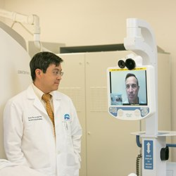 Photo of doctor addressing patient's issue using monitor technology