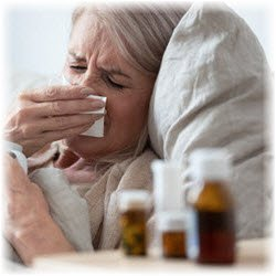 Photo of a woman in bed with flu symptoms with medications on her nightstand