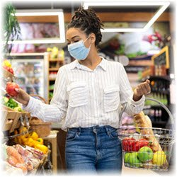 Photo of a masked woman shopping for groceries