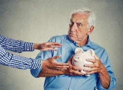 Senior Scams - man holding a piggy bank